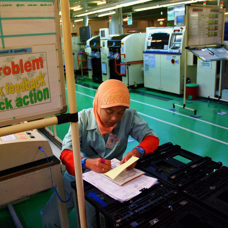 nainen kirjoittaa tehtaalla Kaakkois-Aasiassa.
