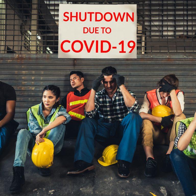 Kuvituskuva: tehtaan työntekijöitä istuu turhautuneen näköisenä koronan vuoksi suljetun tehtaan edessä