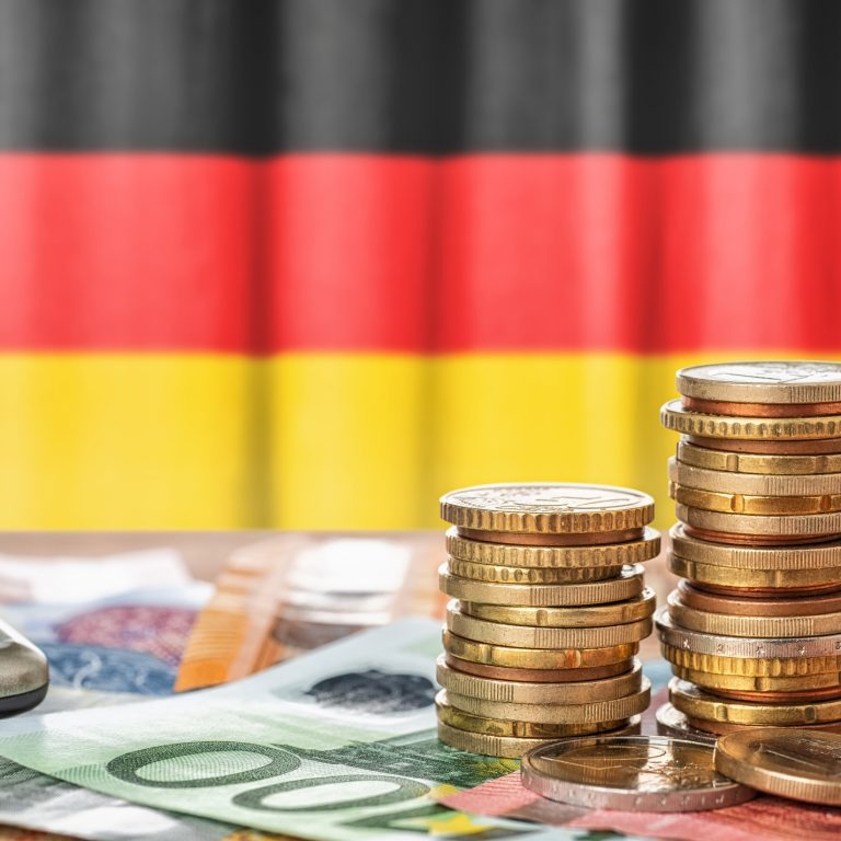 Seteleitä ja kolikoita Saksan lipun edessä