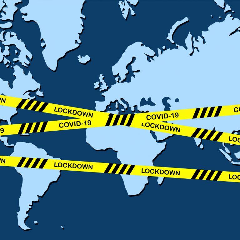 Maailmankartan yli on vedetty koronasulkutilaa kuvaavat varoitustarrat. Kuvituskuva.