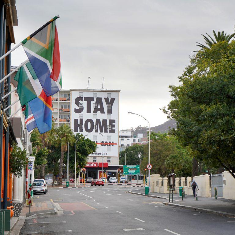 Tyhjä katu ja Stay at home -teksti Kapkaupungissa.