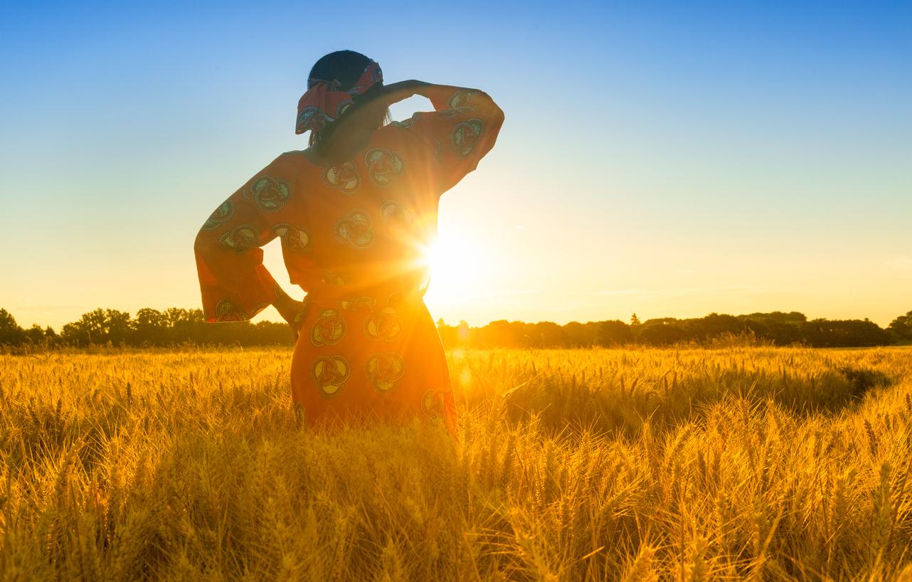 Nainen seisoo viljapellolla ja katsoo auringonnousuun.