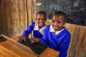 African children using a laptop inside classroom in remote school in southern Kenya.