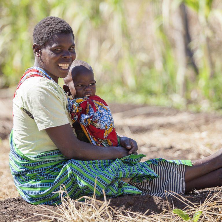 Nainen istuu pellolla lapsi sylissään.