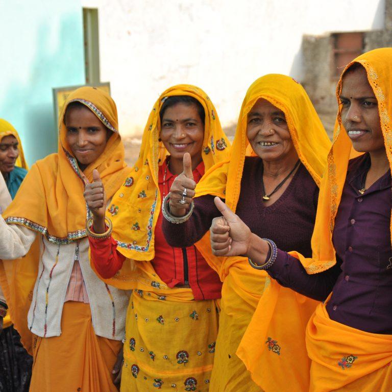 Intialaiset naiset näyttävät peukkua kameralle