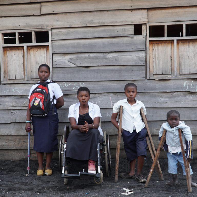 Kuvassa neljä vammaista lasta harmaan puutalon seinustan edessä.