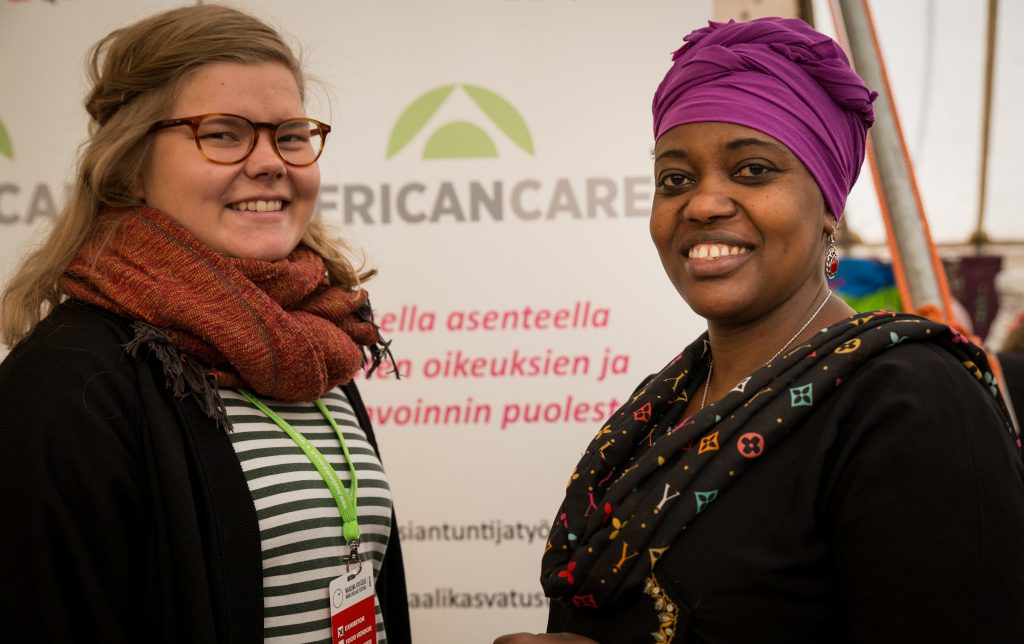 Kaksi naista seisovat vastakkain ja hymyilevät kameraan. Taustalla heidän välissään African care -järjestön roll-up.