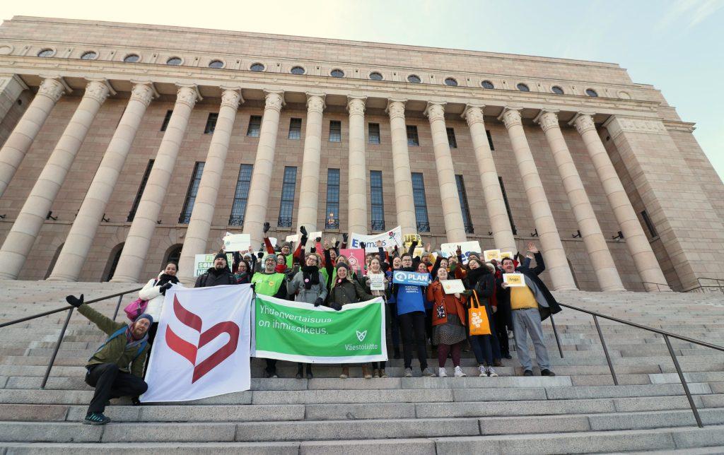 Joukko järjestöihmisiä Eduskuntatalon portailla.