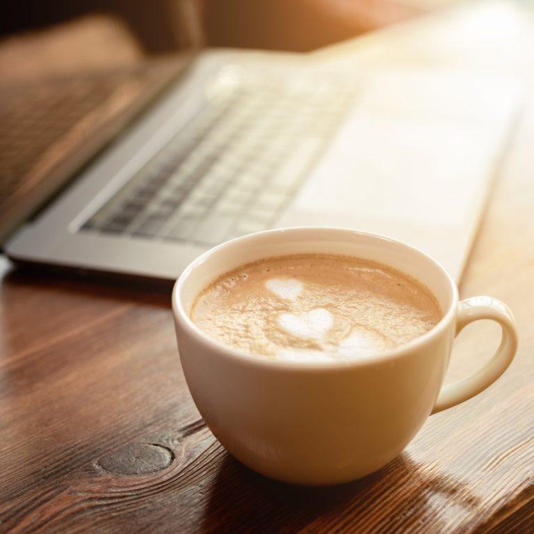 Kahvikuppi puisella pöydällä. Taustalla kannettava tietokone.