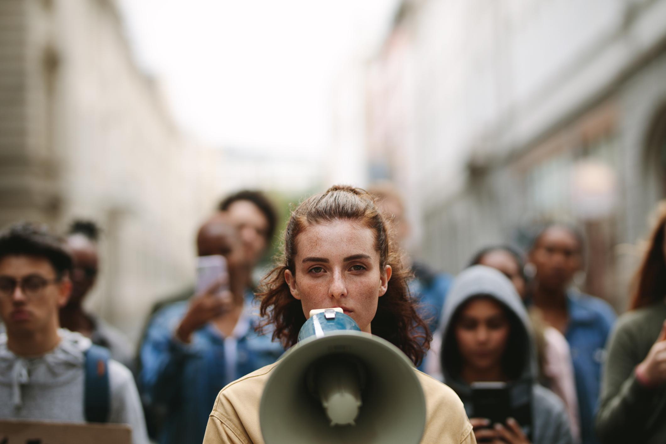 Nainen megafonin kanssa kuvan etualalla. Joukko ihmisiä taustalla.