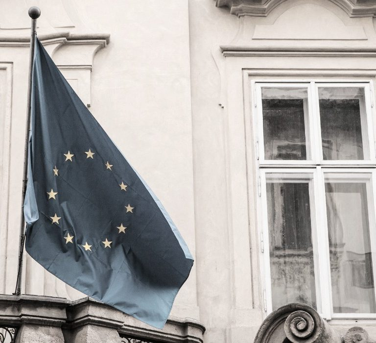 Mustavalkoinen kuva EU-lipustav roikkumassa lipputangossa rakennuksen seinällä.