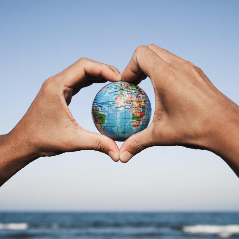 Kuva pienestä maapallosta sydämen muotoon asetettujen käsien sisällä