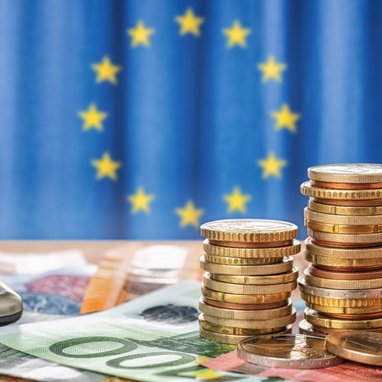 Euroja ja laskin EU-lipun edessä. Kuvituskuva.