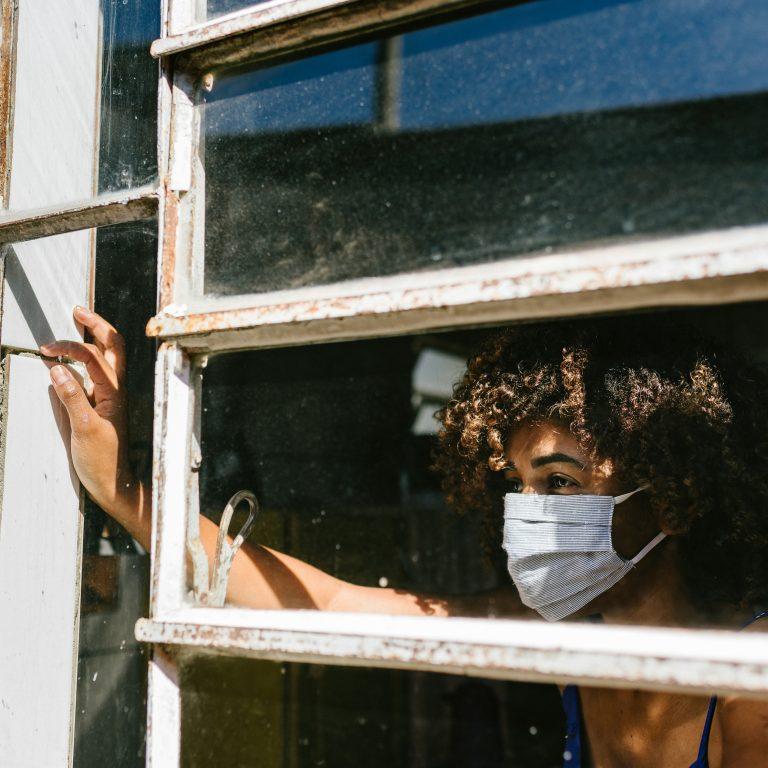 Nainen katsoo maski kasvoilla ulos likaisesta ikkunasta. Kuvituskuva.