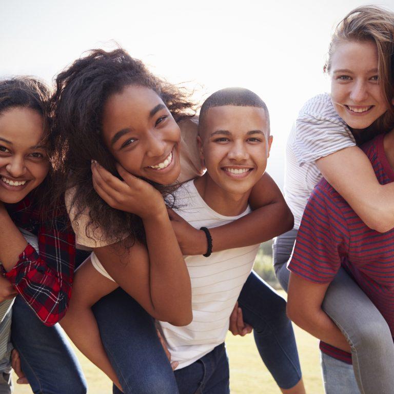 Joukko hymyileviä nuoria eri etnisistä alkuperistä