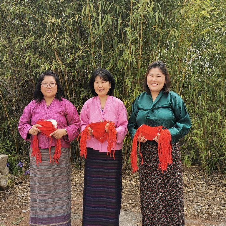 Kolme naista pitävät kankaita käsissään.