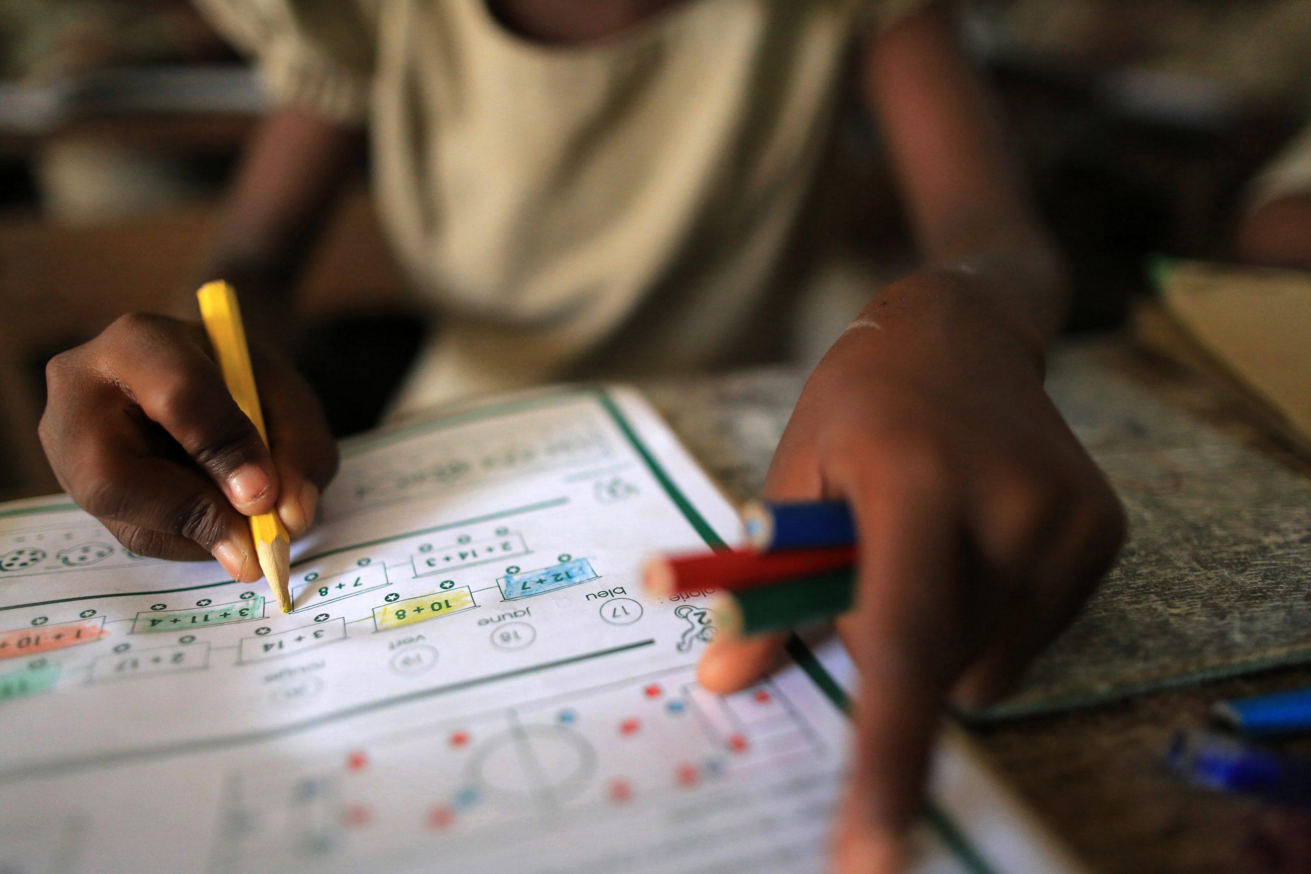 Lähikuva lapsesta tekemässä koulutehtäviä Togossa.