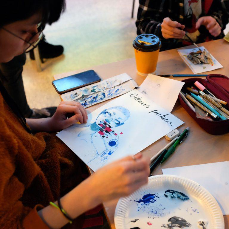 Nuoret maalaavat pöydän ääressä.