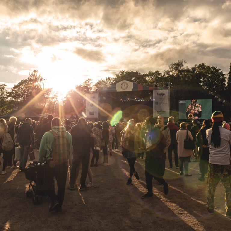 Festivaaliyleisöä festivaalialueella auringonlaskussa.
